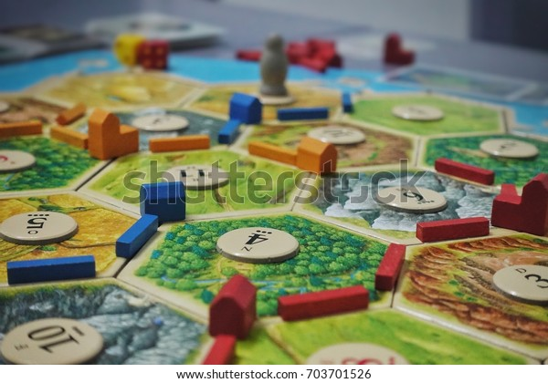 Bangkok, Thailand - Aug 19th, 2017. Board game party with my friends. Settlers of Catan, popular board game. Players are scrambling the area to get more resources and victory points.
