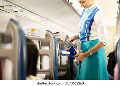 BANGKOK, THAILAND - Aug 27, 2018 - Bangkok Airways flight attendant serve food and drinks to passengers on board