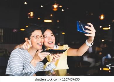 Bangkok, Thailand - Aug 28, 2018: Asian mother and daughter taking selfie photo together with food at restaurant, using S-Pen bluetooth remote shutter on Samsung Galaxy Note 9. Illustrative editorial.