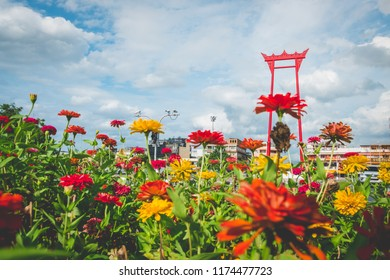 Bangkok, Thailand - Aug 28, 2018 : The Giant Swing with flower foreground and sky background.  (A religious structure that was formerly used in an old Brahmin ceremony)