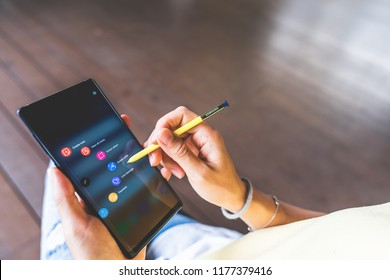 Bangkok, Thailand - Aug 28, 2018: Asian woman hand using yellow S Pen on Samsung Galaxy Note 9 screen, launching screen writing or note application shortcut icon. Illustrative editorial content