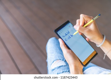 Bangkok, Thailand - Aug 28, 2018: Asian woman hand using yellow S Pen stylus on Samsung Galaxy Note 9 screen, writing reminder or to do list on note application. Illustrative editorial content