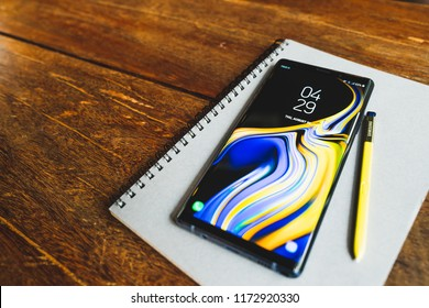 Bangkok, Thailand - Aug 30, 2018: Ocean Blue Samsung Galaxy Note 9 with yellow S pen stylus on a notebook with copy space on wooden table. Illustrative Editorial.