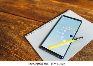 Bangkok, Thailand - Aug 30, 2018: Ocean Blue Samsung Galaxy Note 9 with yellow S pen stylus on a notebook, copy space on wooden table. Screen displaying note and drawing apps. Illustrative Editorial.