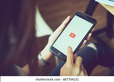 Bangkok, Thailand - August 01, 2017 : woman hands holding apple iPhone 6s on screen displays the Youtube app on the touch screen. YouTube is the popular online video-sharing website.