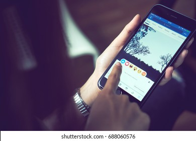 Bangkok, Thailand - August 01, 2017 : hand is pressing the Facebook screen on apple iphone6 ,Social media are using for information sharing and networking.