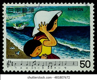 """BANGKOK, THAILAND - AUGUST 06, 2016: A postage stamp printed in Japan shows children and ocean beach, series """"Japan Song"""", circa 1979."""