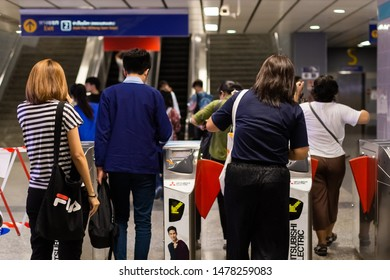 BANGKOK THAILAND - AUGUST 07, 2019: Passengers go through the MRT subway train station ticket barriers in Bangkok Thailand