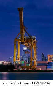 Bangkok / Thailand - August 08 2018: Containers being loaded onto a container ship at dusk.