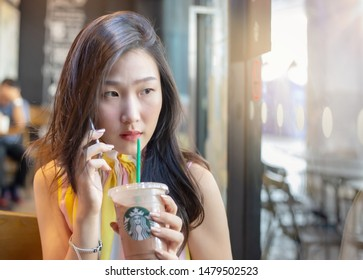 Bangkok, Thailand : August 09, 2019 : Young Asian woman with Starbucks cold beverage using her mobile phone in  Starbucks coffee store. Starbucks is the largest coffee house company in the world.