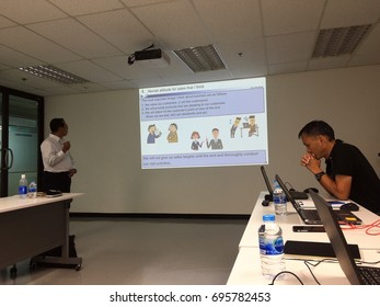 BANGKOK, THAILAND - AUGUST 10, 2017: An Asian man gives a PowerPoint presentation to other people in the meeting room.