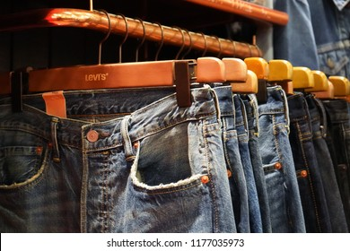 Bangkok, Thailand - August 10, 2018 : Levi's blue jeans hang on a shelf in A Levi's Store. Levi Strauss is one of the world's oldest and most well known jeans manufacturers.