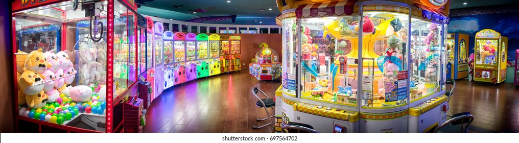 BANGKOK, THAILAND - AUGUST 11: Various kinds of crane crabber arcade machines light and lined up in an arcade in Central shopping mall on August 11, 2017 in Bangkok.