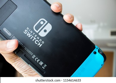 Bangkok, Thailand - August 12, 2018 : A hand holding the Nintendo Switch show the Nintendo  Switch Logo.