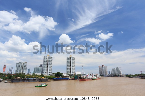 Bangkok, Thailand. August 13, 2017. Towboat or Tugboat Sailing in the Chao Phraya River with Cargo Marine Boat Docked at Port Background and Condominium with Beautiful Cloud Blue Sky .