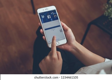 Bangkok, Thailand - August 13, 2018 : hand is pressing the Facebook screen on apple iphone 6 ,Social media are using for information sharing and networking.