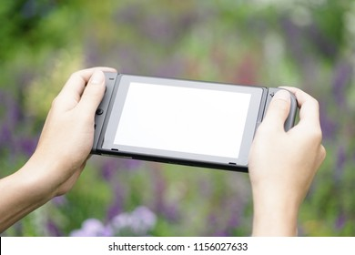 Bangkok, Thailand - August 13, 2018 : A photo of 2 hands holding Nintendo Swtich while playing anonymous game in the garden. Empty screen for your personalized game or screen. Soft focus.