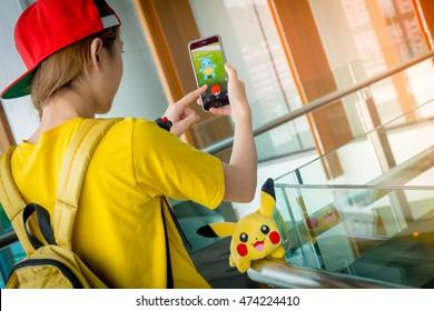 BANGKOK, THAILAND -? August 14,2016:  Trainer girl playing pokemon , pokemon ball and Pokemon Go mobile game app on smart phone gadget ,Lighting with sun flare