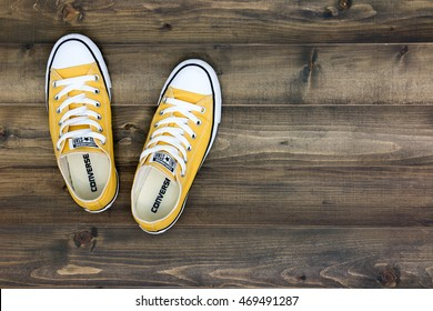 Bangkok, Thailand, August 16, 2016: Yellow Converse shoes on wooden planks. Minimal concept.