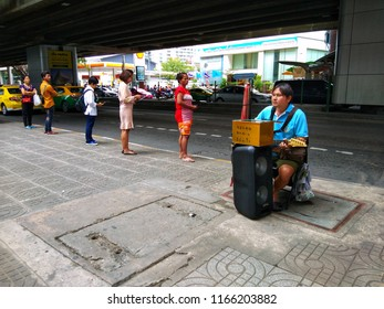 Bangkok, Thailand - August 17, 2018: A blind man is playing guitar on the street. Street performance or busking is the act of performing in public places for gratuities.