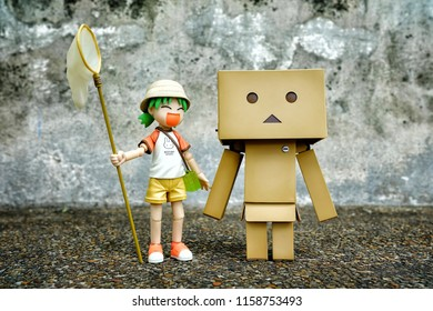 BANGKOK, THAILAND - AUGUST 18, 2018: Miniature Yotsuba Koiwai and Danboard anime figure standing on pebble stone ground with Grunge Concrete Wall. It's famous Japanese comedy manga series.