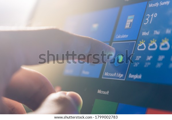 Bangkok, Thailand - August 20, 2020 : Computer user touching on Microsoft Edge, a web browser developed by Microsoft, icon to open the program.