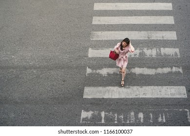 Bangkok Thailand - August 25, 2017: Young woman with shoulder bag walking across the crosswalk at the junction street of city, Pedestrian safety, Aerial view