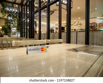 BANGKOK, THAILAND - AUGUST 25, 2018: Closeup of restaurant table with a reservation plaque and MasterCard Credit Card logo. Siam Paragon department store. Finance and spending.