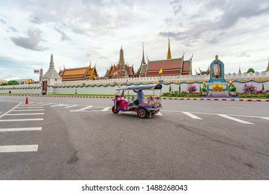 BANGKOK, THAILAND -  AUGUST 25, 2019 : Traditional Thai Taxi Tuk Tuk Parking For Wait a Tourist Passenger At Ratchadamnoen Road With Wat Phra Kaew Temple of Emerald Buddha Background In Bangkok