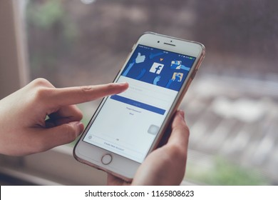 Bangkok, Thailand - August 28, 2018 : hand is pressing the Facebook screen on apple iphone 6 ,Social media are using for information sharing and networking.
