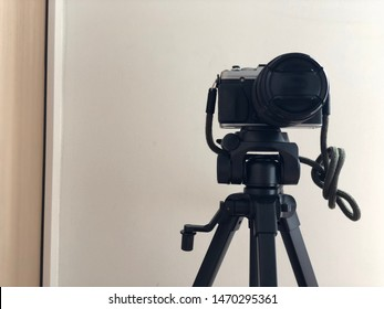 BANGKOK, THAILAND. AUGUST 28, 2019: the close up of complete camera set which consists of Fuji XE1 camera and Fujinon lens 18-135mm, and tripod.