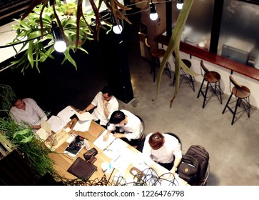 Bangkok Thailand August 29, 2017 : A night meeting of  young man working team at a meeting table in 24 hours opening  downtown cafe  showing a trendy all day all night laptop lifestyle.