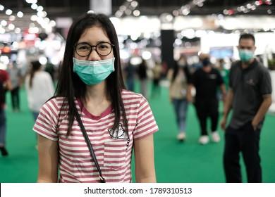 Bangkok, Thailand - August 3, 2020 : Beautiful Asian women at a trade show. She is wearing a mask.