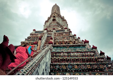 BANGKOK, THAILAND - AUGUST 3: Buddhist monks walk up stairs of Wat Arun temple, in Bangkok on August 3, 2012. Buddhism is Thailand official religion and is the religion of more than 90% of its people