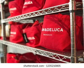 BANGKOK, THAILAND - AUGUST 31, 2018 : Red canvas fabric bag of DEAN & DELUCA brand on shelf for display and sale as souvenir at coffee shop, Mahanakhon cube branch, Bangkok Thailand.