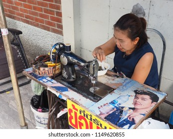 BANGKOK, THAILAND - AUGUST 4, 2018: A woman takes a short break and eats some  street food while sitting behind her sewing machine on August 4, 2018 in Bangkok, Thailand.