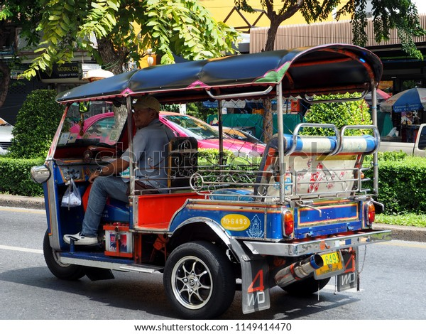 BANGKOK, THAILAND - AUGUST 4, 2018:  A tuk tuk driver looks for customers on Silom Road on August 4, 2018 in Thai capital Bangkok.