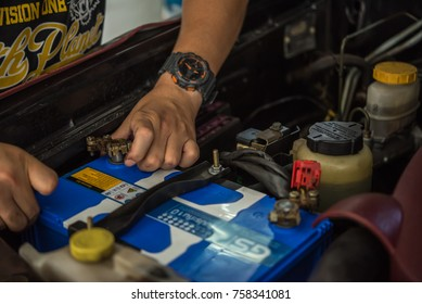 Bangkok, Thailand - August 5, 2017 : Unidentified car mechanic or serviceman checking a car battery for fix and repair problem at car garage or repair shop
