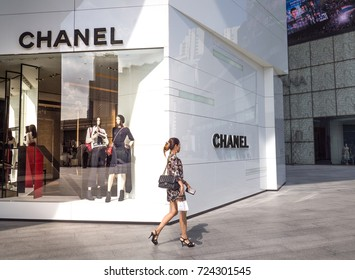 BANGKOK THAILAND , CHANEL Boutique store at The Emquartier Department store on September 9 2017, CHANEL Logo in front of shop woman with chanel hand bag walking past in front of the shop