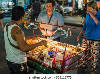 Bangkok, Thailand - Circa December 2016 - Tourists buying fried insects on the streets of Khao San Road in Bangkok, Thailand