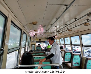 BANGKOK, THAILAND, DEC 5, 2018: Ticket taker on the old public bus in Bangkok, Thailand