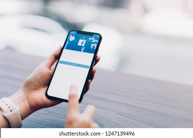 Bangkok, Thailand - December 03, 2018 : hand is pressing the Facebook screen on apple iphone x ,Social media are using for information sharing and networking.