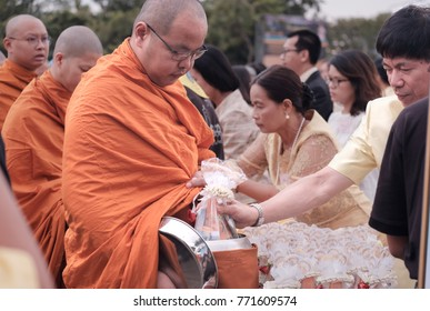 BANGKOK, THAILAND - DECEMBER 05: View of people give alms to Buddhist monk. Traditions of Merit, Father's Day, Royal palace of Ananta Samakhom on December 05,2017 in Bangkok, Thailand.