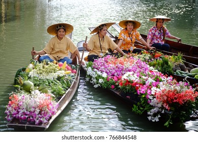 BANGKOK, THAILAND - December 1, 2017: Unidentified female vendors sell fruits and flowers floating in boats at RAMA IX Park, Bangkok, Thailand.