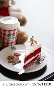 Bangkok, Thailand - December 1, 2018 : A photo of red velvet Christmas cake and seasonal Starbucks coffee in takeaway paper cups served only during the Christmas. Soft focus on the red velvet cake.
