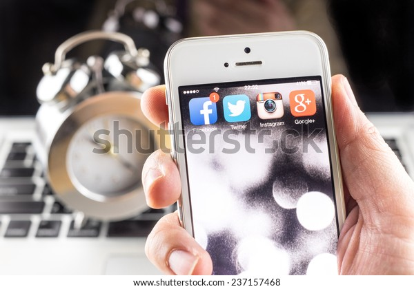 Bangkok, Thailand - December 10, 2014: Hand holding iPhone with social media applications on screen ,Social media are using for information sharing and networking.