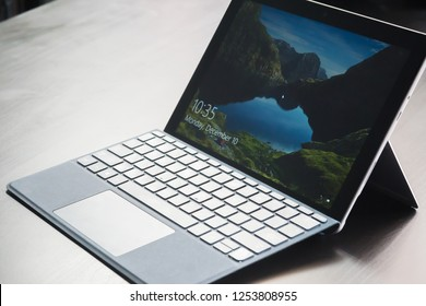 BANGKOK, THAILAND DECEMBER 10 2018: The Microsoft Surface go tablet - computer with Microsoft in Windows 10  screen and Thai keyboard bluetooth on wooden desktop in store