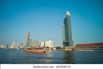 BANGKOK, THAILAND - DECEMBER 10: Chao Phraya River include modern tower and public boat, It's the major river in Thailand, with its low alluvial plain forming the centre of the country on Dec 10, 2020