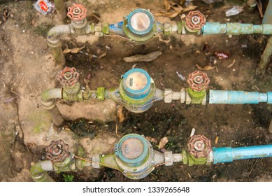 Bangkok, Thailand- December, 13, 2018 : Water meter on concrete with home and green nature background.Open cover of water meter to check counter number of water consumption.Bangkok, Thailand