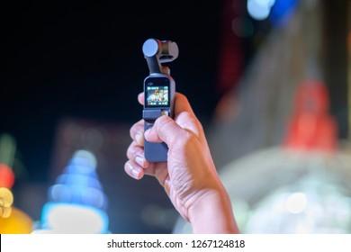 BANGKOK, THAILAND - December 16: Central World Bangkok on December 16,2018 in Bangkok, Thailand. Man hand holding DJI Osmo Pocket gimbal camera
